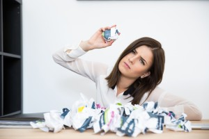 Businesswoman sitting at the table with trash paper